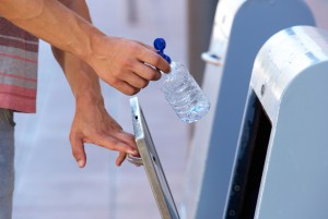 Male hand putting plastic bottle in recycling bin